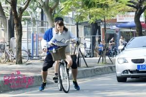 高以翔乘坐王水林自行車囧態百出,拍攝地點在興大籃球場前馬路。(圖華宇國際娛樂有限公司提供)