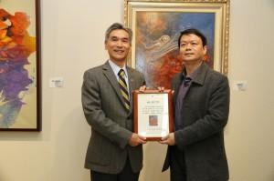 莊明中(右)致贈畫作「慶豐年」予興大藝術中心典藏,由興大薛富盛校長頒發感謝狀